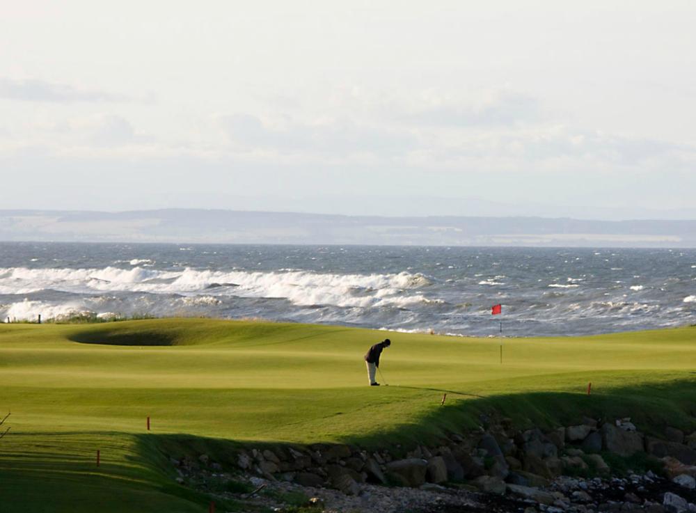 Golfeur sur le green du trou signature sur le parcours de Kingsbarns