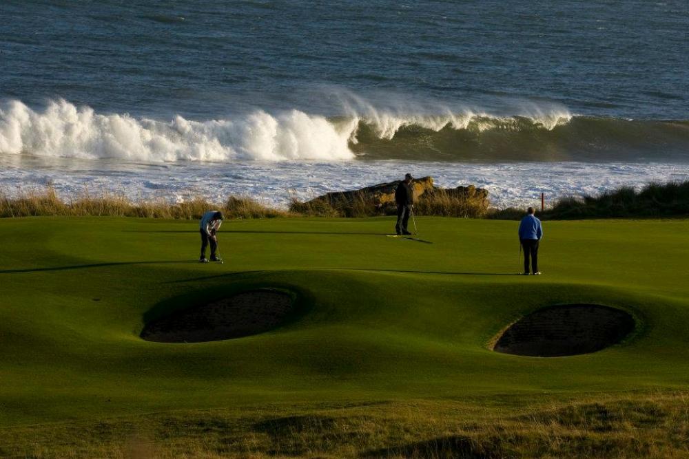 Golfeurs au putting  et vague sur le parcours du Royal Dornoch