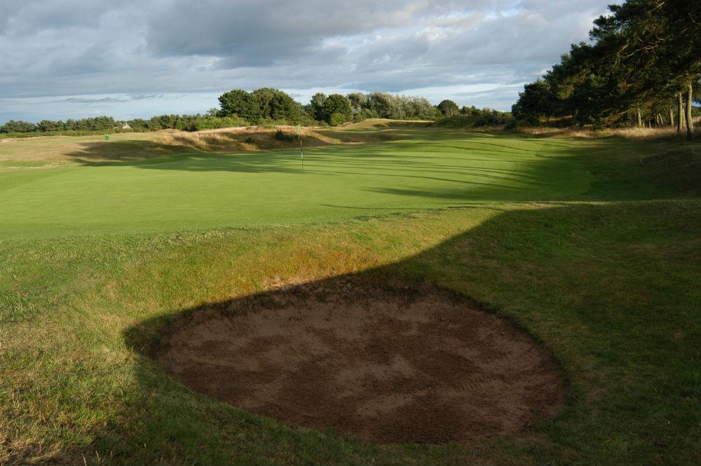 Le green et un bunker du golf de Scotscraig.