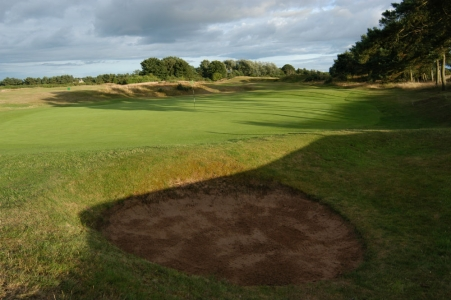 Le green et un bunker du golf de Scotscraig.